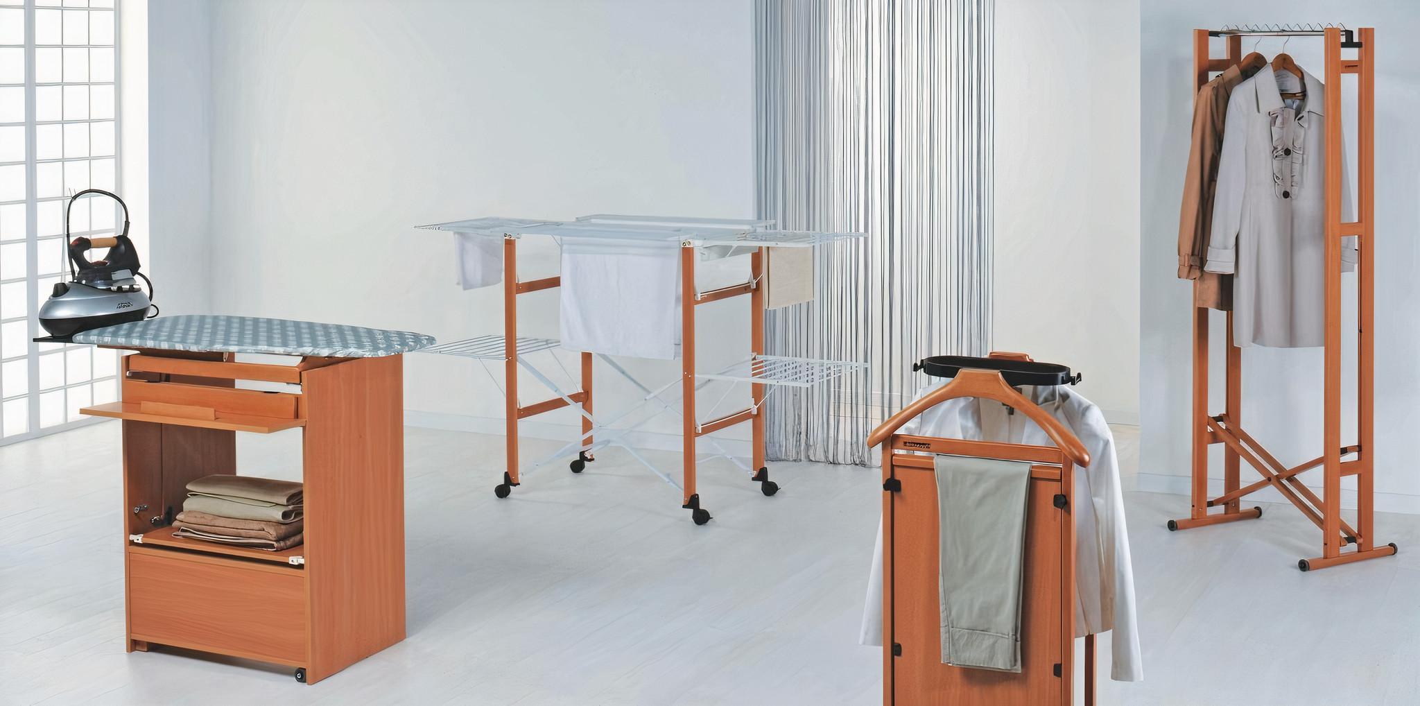 Деревянная мебель: Гладильная доска, сушилка для белья, тумба и напольная вешалка от бренда Foppapedretti, белые стены и пол, окно