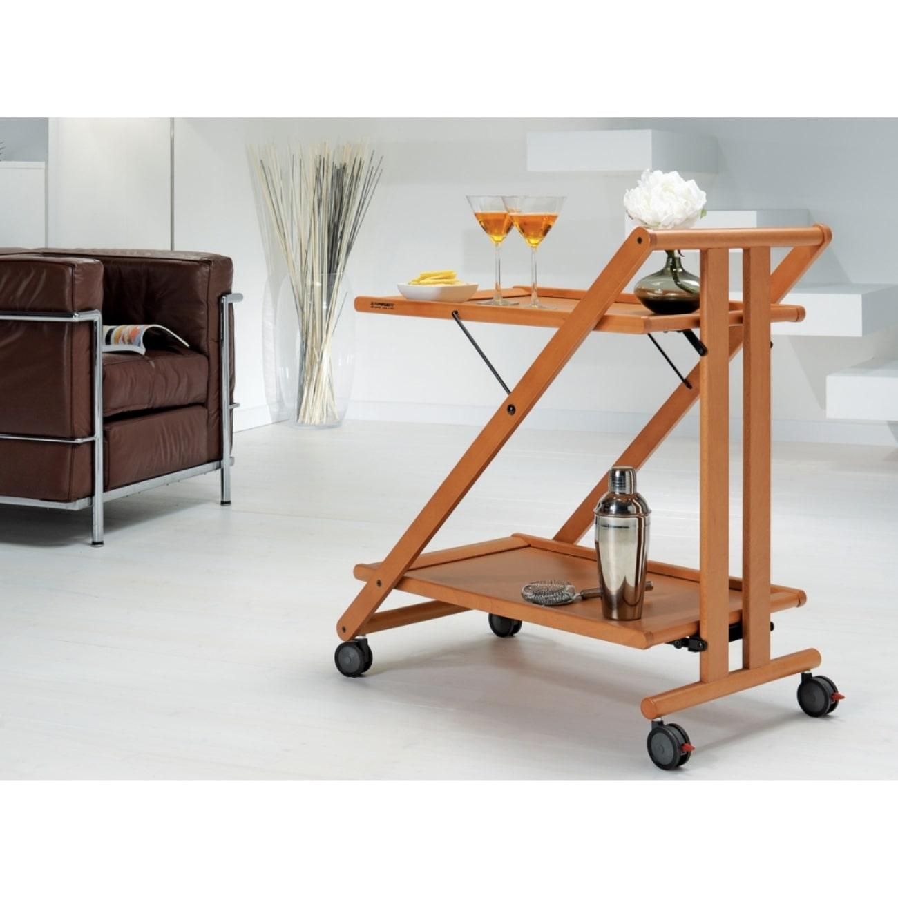 Итальянский Сервировочный столик Sprint Foppapedretti деревянный цвет Орех на колесиках, белый пол и стены, темное мягкое кресло, на столике 2 бокала, маленькая ваза с цветком, металлическая бутылка